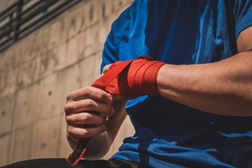 Person taping their hands to get ready for a fight.
