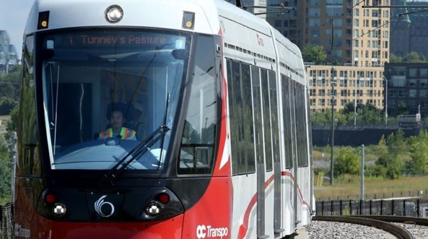 Ottawa light-rail train with a city skyline in the background.