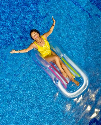 Women lounging on a floating device in a pool.