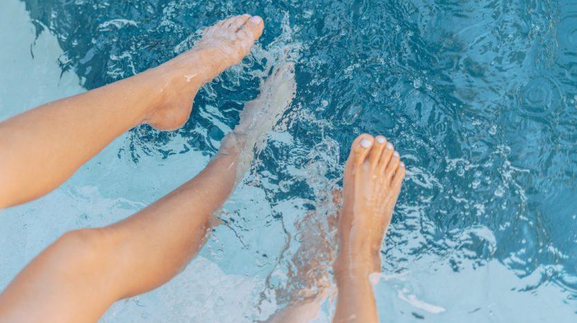 Feet splashing in pool water.