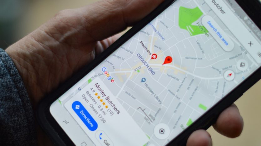 A hand holding a phone looking at a google map application.